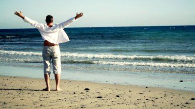 stock-footage-man-at-the-beach-raising-hands-to-the-sky-freedom-concept